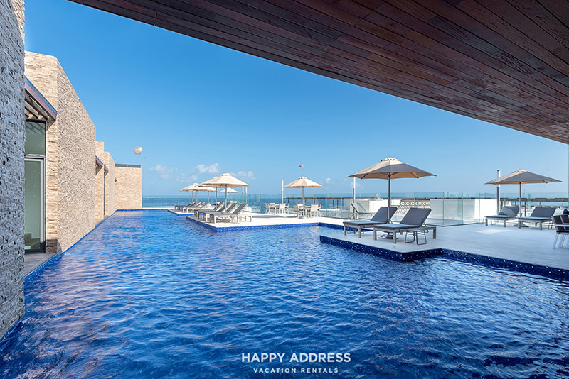 Pool with umbrellas looking over Caribbean
